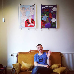 Bitte Andersson sitter i guldgula soffan under sina största affischer, vinkandes med stort leende. Affischerna föreställer en grå person som duschar och gör sig fin, den andra två äldre kvinnor som kysser varandra.