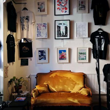 Solen lyser in på den guldgula sammetssoffan och Rudy Loewes fina tavlor och T-shirtar.
