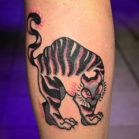 Tatuering av Bahicho. Svart och grå och rosa tiger som kutar rygg på ett ben.