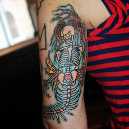 Tatuering på arm av Soledad Aznar. Skelettsjöjungfru i old school stil med långt hår, gula ögon och turkost ljus bakom.