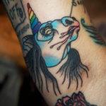 Tatuering på arm av Sara Swanson. En blå ursinnig enhörning med regnbågshorn och rosa dreggel ur munnen. Svart svallande hår.