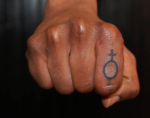Knuten näve med tatuering av kvinnotecken på pekfingret.