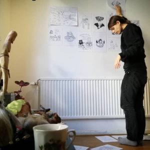 Hanna Gustavsson som hänger upp teckningar inför sin utställning. Hela golvet är täckt med teckningar och i hörnet syns statyer och trollfigurer.