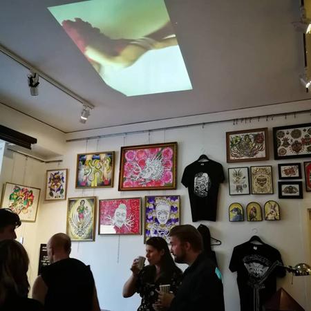 Besökare tittar på konst, färgglada och arga demoner på väggarna och filmprojektion i taket av dansande ben i kort röd kol och fotbollsstrumpor.