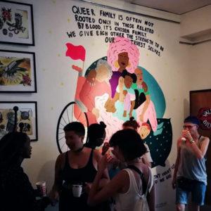 Mingel på Rudy Loewes utställning med Rudy i förgrunden. I bakgrund väggmålning av grupp människor med slutna ögon, vilandes, och texten Queer Family is often not rooted only in those related by blood. It´s chosen family. We give each other the strength to be our truest selves.