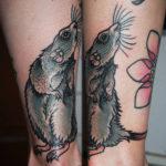 Tatuering på vrist av Soledad Aznar. En nyfiken grå råtta i old school stil med långa morrhår nosar uppåt benet.