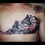 Tatuering över bröst av Soledad Aznar. Stora svart berg täcker ärr i gravyrstil. På axeln en kompass.