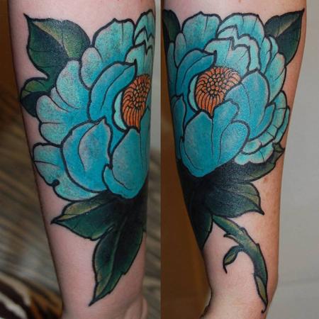 Tatuering över underarm av Soledad Aznar. En stor turkosblå pion med mörkgröna blad och kraftig stjälk.