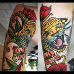 Tatuering på arm av Soledad Aznar. Färgstark old school geopardhuvud med röda blommor och banderoll runtomkring.