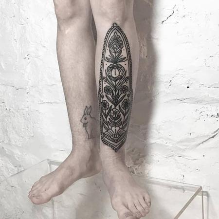 Tatuering av queera tatueraren Ciara Havishya. Ortnamentalt floralt motiv på smalben.