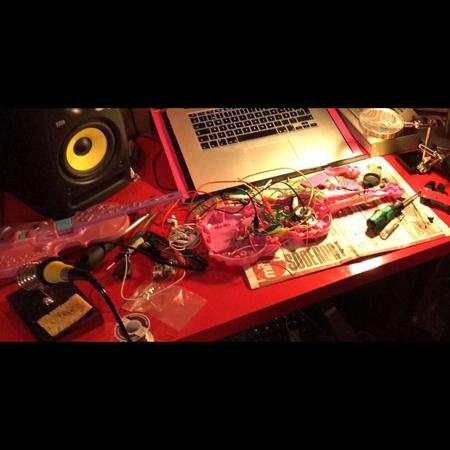 Bild till workshopen Queering Circuits. En isärdelad rosa leksaksgitarr väntar på att få nytt liv.
