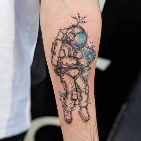 Tatuering av queer tatuerare Cynthia Sobraty. Rymdastronaut i sketch stil, rosa och blå.