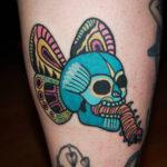 Old school tatuering av tatuerare Soledad Aznar. Dödskalle med fjärilsvingar och tjock larv som kommer ut ur munnen.