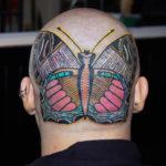 Färgglad nattfjäril över bakhuvud, av tatuerare Soledad Aznar.