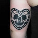 Old school tatuering av tatuerare Soledad Aznar. Jättelycklig dödskalle i hjärta.