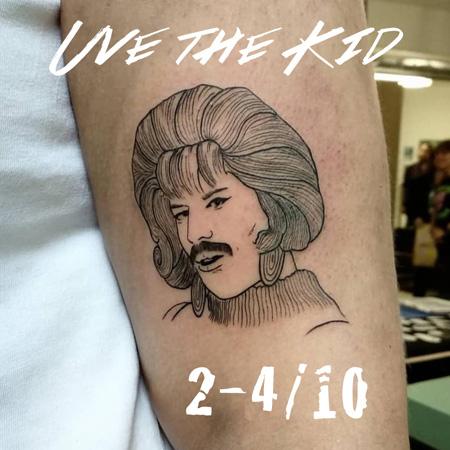 Tatuering av queer tatuerare Uve the Kid. Linjärt porträtt av Freddie Mercury i peruk och med mustasch.