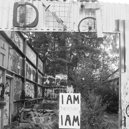 Svart vitt foto bakgård med figur som håller upp en skylt framför sig: I am therefore I am