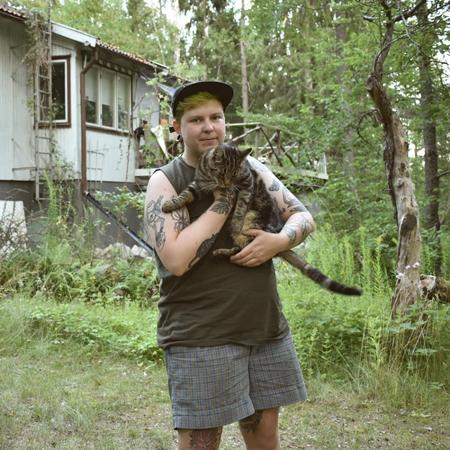 Queer tatuerare Alex står i grönska med en katt i famnen.