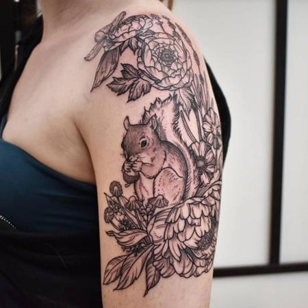 Tatuering på överarm av queer tatuerare Alex , ekorre bland blommor i gravyr stil.