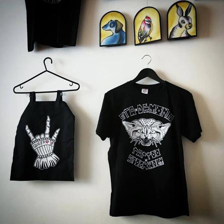 Upphängt på vägg; väska med handskprydd skeletthand med texten queer och T-shirt med glad katt.
