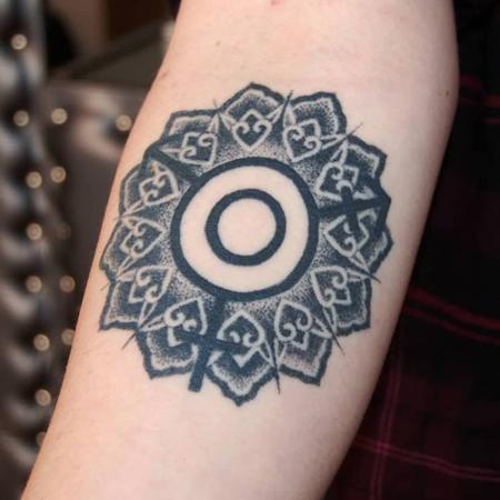 Tatuering på underarm av Soledad Aznar. Mandala i dotwork stil med transsymbol som centrum.