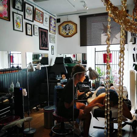 Bahia tatuerar en person som ligger avslappnad på en brits. Solen lyser in i rummet, färgglada tavlor på väggarna och pärldraperi i förgrunden.