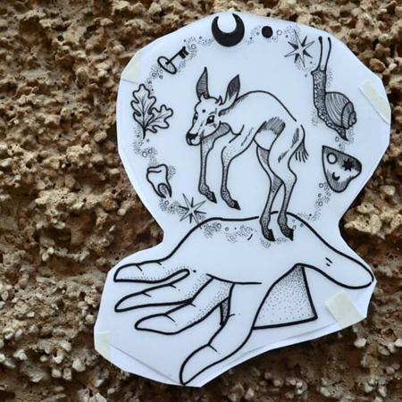 Motiv för tatuering av Bahicho. Ovanför en öppen hand flyter en energicirkel av djur och växter runt . Mitt i allt hoppar ett rådjurskid.