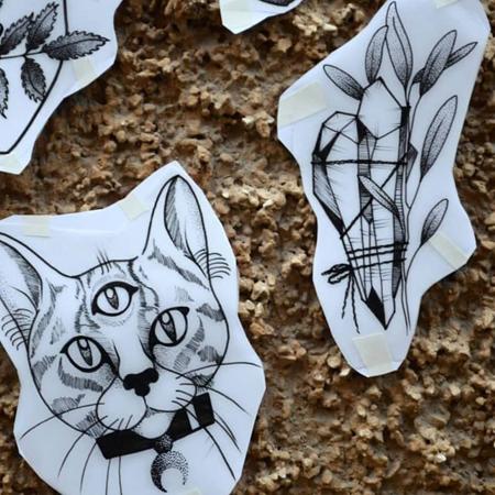 Motiv för tatuering av Bahicho. En tigerrandig katt med tre ögon och månhalsband bredvid hopbundna kristaller.