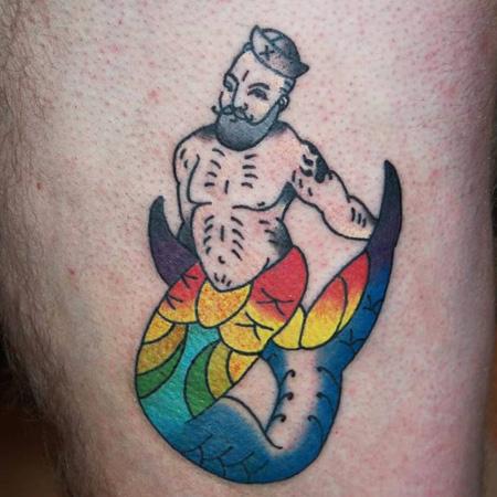 Tatuering på lår av Sara Swanson. En hårig skäggig murman med den stora fenan i regnbågsfärger och skeppsmössa.