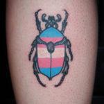 Tatuering på vad av Soledad Aznar. En skalbaggen med transflaggans färger över ryggen i old school stil.
