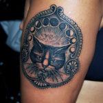 Tatuering på arm av Soledad Aznar. Svart katt med månens gång och dekorativt inramad i blackwork och dotwork stil.