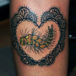 Tatuering på ben av Sara Swanson. Spetshjärta med grön tusenfoting i mitten.