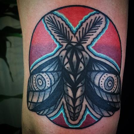 Tatuering av Kai Knowfolly. Old school nattfjäril över en röd och lila cirkel och med turkosblå aura.