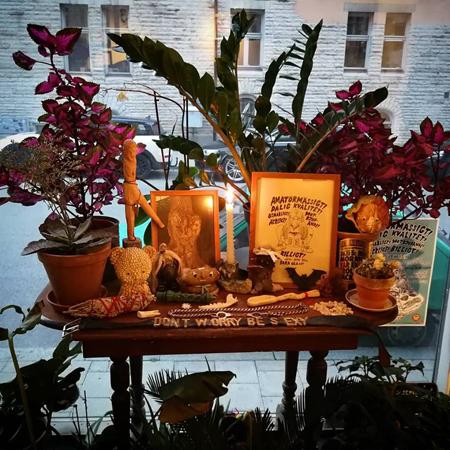 Altare i stort fönster mot gatan med sten -och snäcktroll, statyer, ben, tänder omringade av växter. I förgrund skärp med texten Don´t worry be sexy.