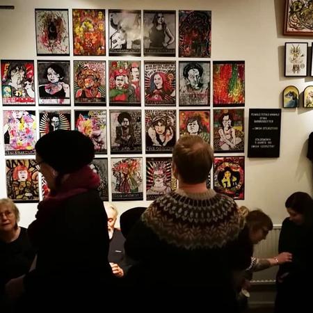 Besökare tittar på Stina Barbrosdotters affischvägg med idolbilder; färgglada och starka porträtt av Valeri Solana, Karin Boye, Grace Jones mfl.
