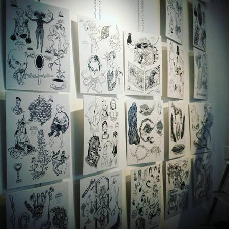 Motiv för tatuering hängandes över en hel vägg. Sagoväsen, trasiga och ihopsydda figurer, sömmar och saxar.