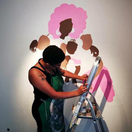 Rudy Loewe på en stege målandes en stor väggmålning. Hen målar fram en grupp personer som håller om varandra, den mest framträdande med stort rosa hår, omfamnandes de andra som en beskyddare.