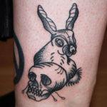 Tatuering på ben av Sara Swanson. Hare med satanistiskt kors i pannan bredvid gråtande dödskalle i blackwork och dotwork stil.