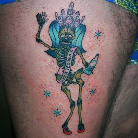 Tatuering på lår av Sara Swanson. En berusad Miss Universum i form av grönt skelett vinkar med flaska i handen och stor rosa juvelkrona på huvudet. På banderollen står det Miss Tequila.