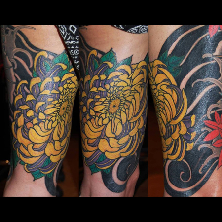 Tatuering över lår av Soledad Aznar. En stor lila och gul krysantemum virvlar bland vind och vågor i japansk stil.