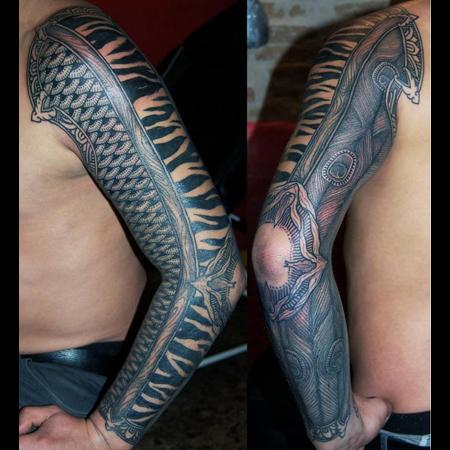 Tatuering hel sleeve i blackwork stil. Olika grafiska gjurmönster som zebra, fjäll och påfågelfjädrar. Runt armbågen en slags organisk käft.