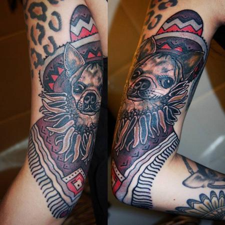 Tatuering på arm av Soledad Aznar. Old school porträtt i färg av chihuahua med mexikansk hatt och torkade chilis som halsband.