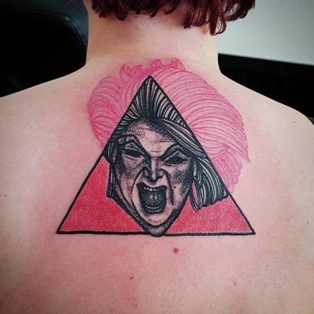 Tatuering på rygg av Soledad Aznar. Porträtt i blackwork/dotwork av Divine över en rosa triangel. Håret som sträcker sig utanför triangeln skiftar från svart till rosa.