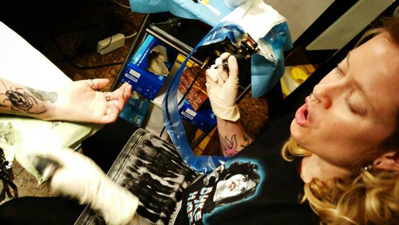 Sara tatuerar en kackerlacka. Pratandes och med Dyke Hard T-shirt.