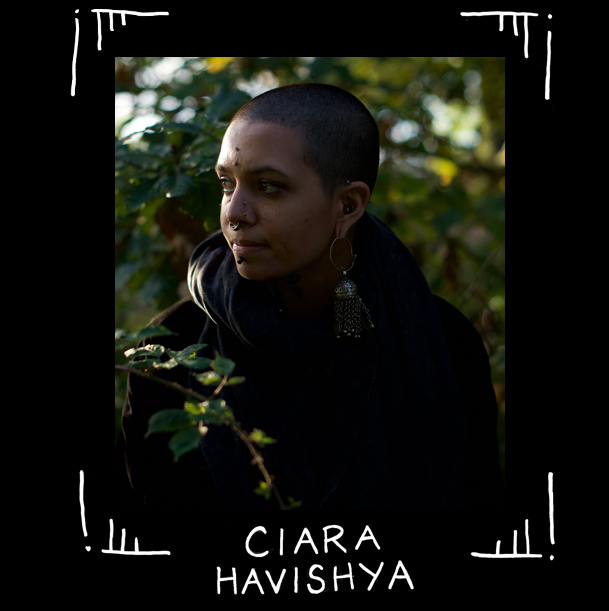 Foto av queer tatuerare Ciara Havishya, med rakat huvud mot grönlummig bakgrund.