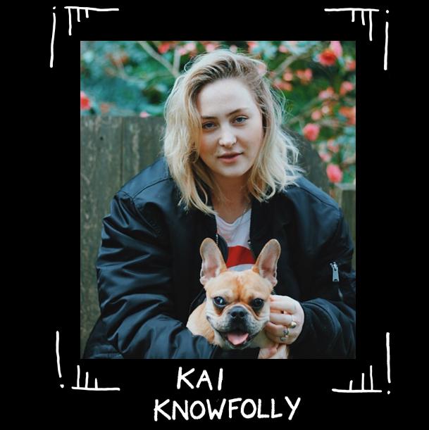 Foto av queera tatueraren Kai Knowfolly med söt hund i knät och blomster i bakgrund.