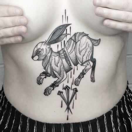 Sternumtatuering av queera tatueraren Ciara Havishya. En tredelad hare med blod som droppar över tre bultar i blackwork dotwork stil.