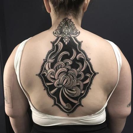 Ornamental tatuering av queera tatueraren Ciara Havishya. Stor krysantemum på rygg i dotworkstil.