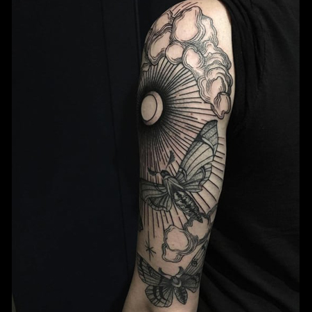 Tattoo by queer tattoo artist Ciara Havishya; Moth flying in cloudy sky in black work style.
