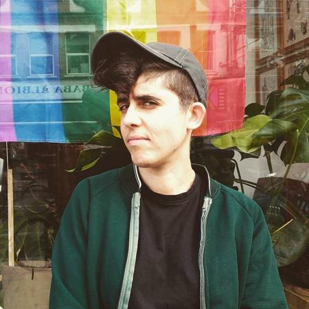 Queer tatuerare Uve the Kid står med keps framför ett fönster med stor regnbågsflagga.
